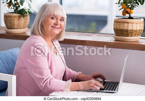 Pleasant elderly lady typing on her laptop - csp43393694