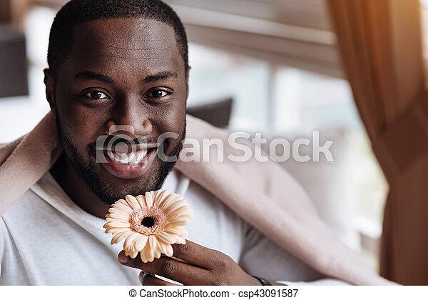 Pleasant young African American man holding the flower - csp43091587