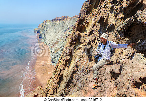 Pleased nature photographer is sitting on the edge of cliff. - csp49216712