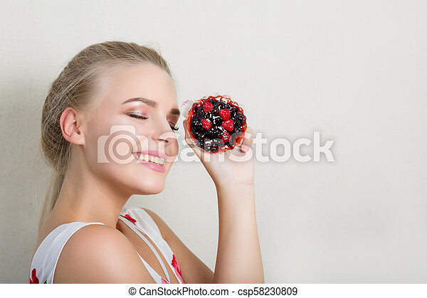 Pleased smiling blonde model having fun with a sweet cupcake with berries. Space for text - csp58230809