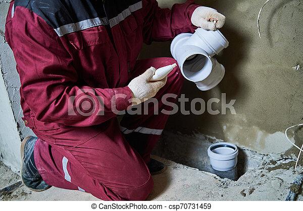 El plomero instala tuberías de aguas residuales en el sistema de alcantarillado - csp70731459