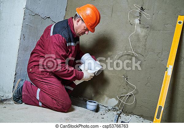 El plomero instala tuberías de aguas residuales en el sistema de alcantarillado - csp53766763