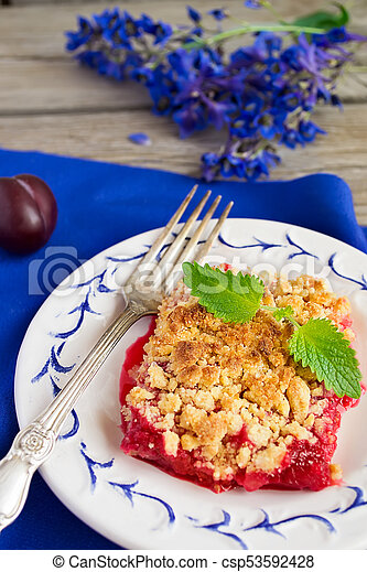 Plum crumble on the wooden background with blue flowers - csp53592428