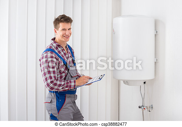 Plumber checking electric boiler. Young male plumber holding ...
