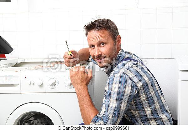Plumber fixing broken washing machine - csp9999661