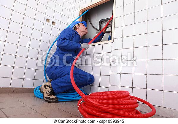 Plumber installing piping - csp10393945
