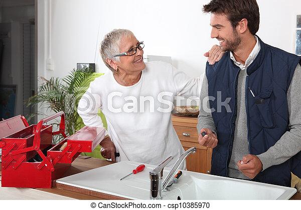 Plumber repairing sink for old lady - csp10385970