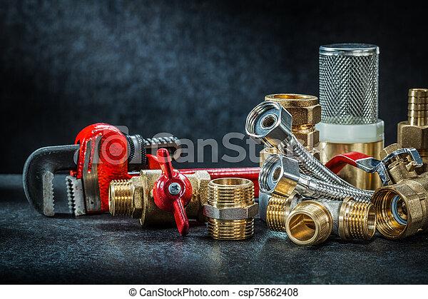 plumbing brass pipe connectors on dark background - csp75862408