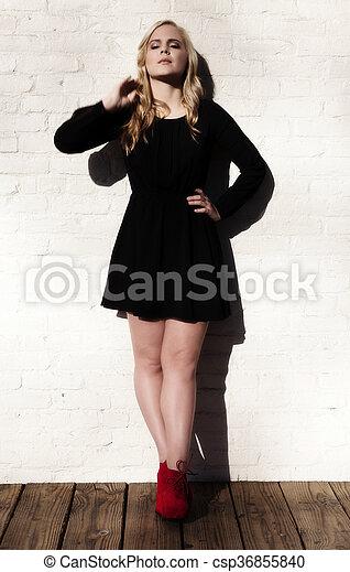 Plump Caucasian Blond Woman Black Dress White Wall - csp36855840