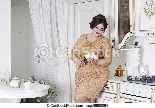 Plus size fashion model on kitchen, fat woman on luxury interior, overweight female body - csp49986084