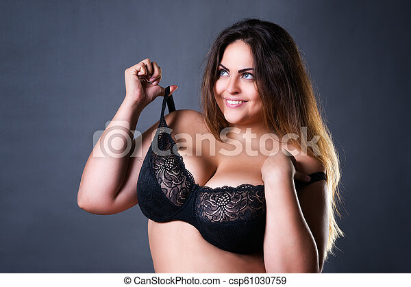 Plus size sexy model in black bra, fat woman with big natural breast on gray studio background, overweight female body - csp61030759