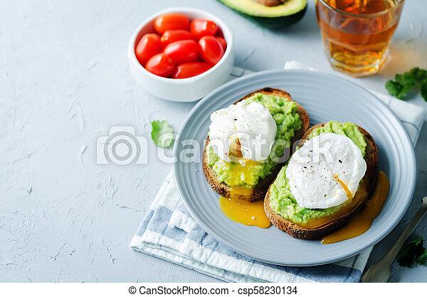 Poached egg Avocado Rye Toasts - csp58230134