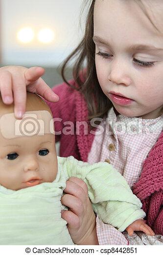 La niña le puso una escayola en la frente a su muñeca - csp8442851