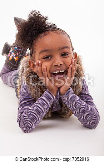 Retrato de una niña africana recostada en el suelo, sobre fondo blanco, gente negra - csp17052916