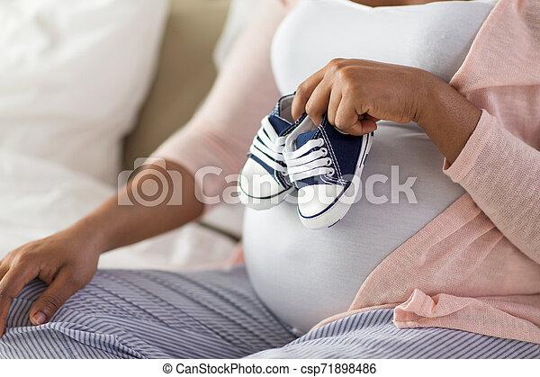 Mujer africana embarazada con botas de bebé - csp71898486