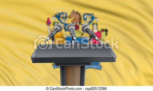 Podium lectern with microphones and New Jersey flag in background - csp82512386