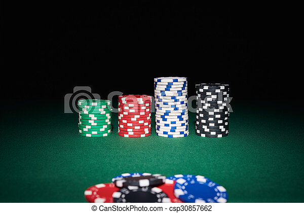 Poker chips on table - csp30857662 & Poker chips on table in casino with black background.