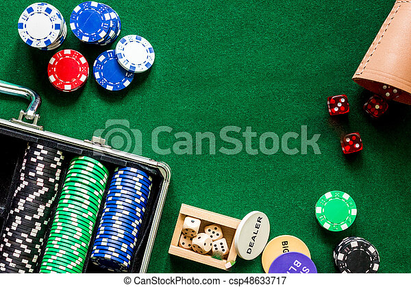Poker set in a metallic case on a green gaming table top view.