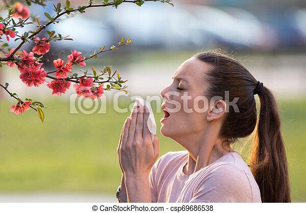 Mujer estornudando por la alergia al polen de primavera - csp69686538