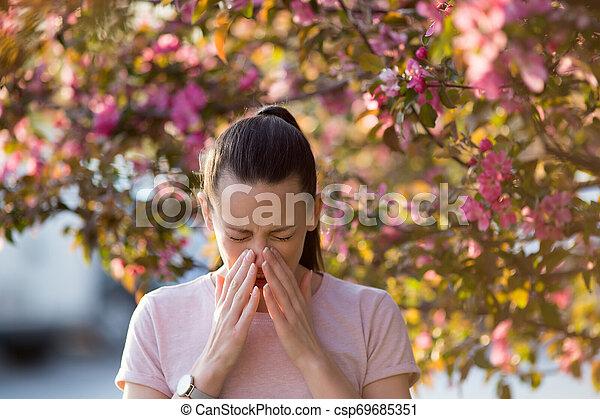 Mujer estornudando por la alergia al polen de primavera - csp69685351
