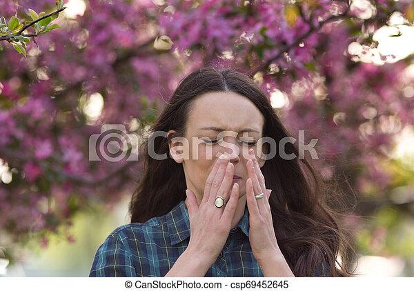 Mujer estornudando por la alergia al polen de primavera - csp69452645