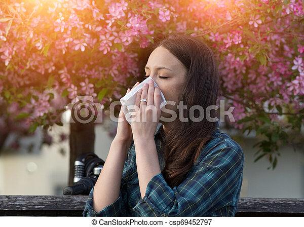 Mujer estornudando por la alergia al polen de primavera - csp69452797