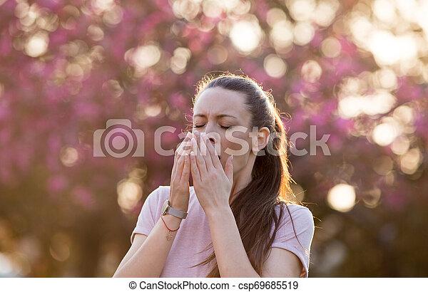 Mujer estornudando por la alergia al polen de primavera - csp69685519