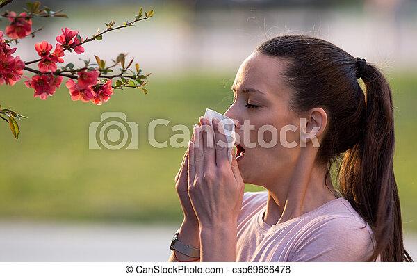 Mujer estornudando por la alergia al polen de primavera - csp69686478