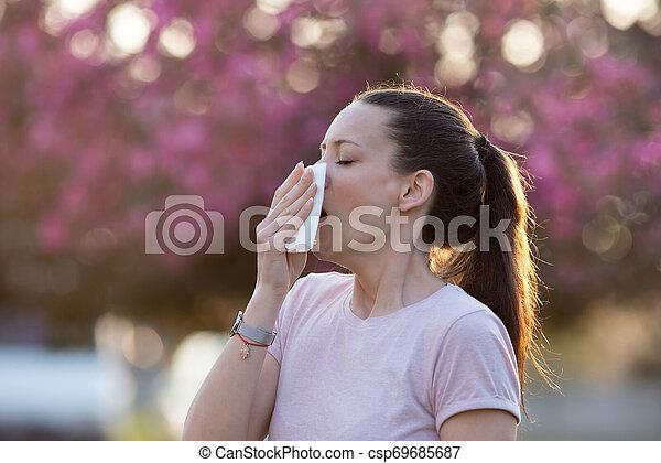 Mujer estornudando por la alergia al polen de primavera - csp69685687