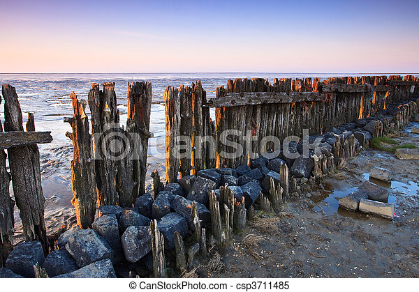 Poles in the ocean at sunset - csp3711485