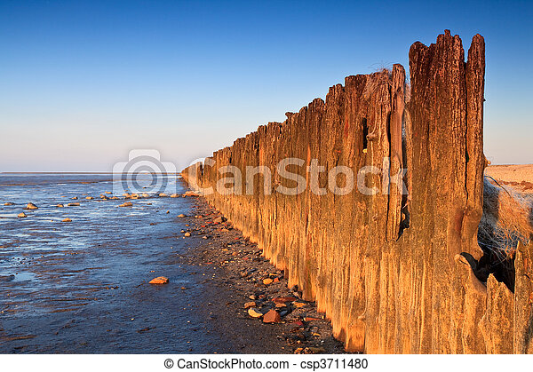 Poles in the ocean at sunset - csp3711480