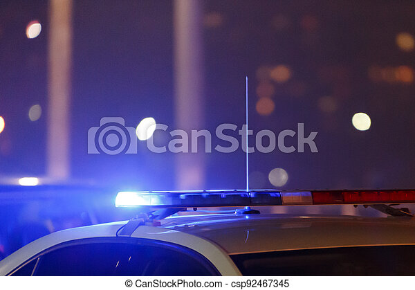 police car lights at night in city with selective focus and bokeh - csp92467345