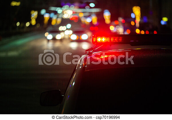 police car lights at night in city with selective focus and bokeh - csp70196994
