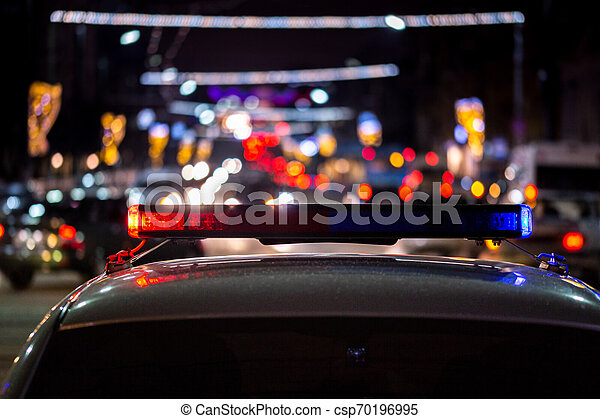police car lights at night in city with selective focus and bokeh - csp70196995