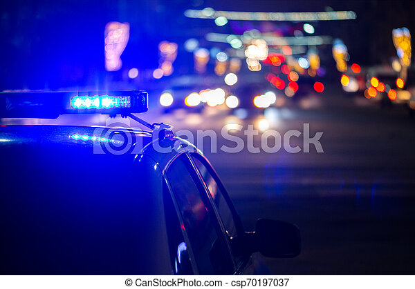 police car lights at night in city with selective focus and bokeh - csp70197037