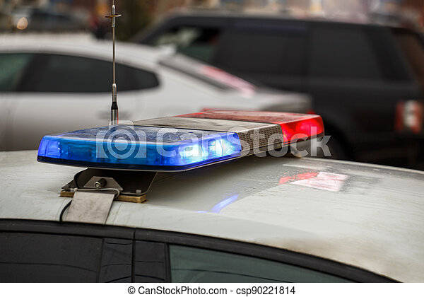police car lights in city street at winter day with cars traffic in blurry background - csp90221814