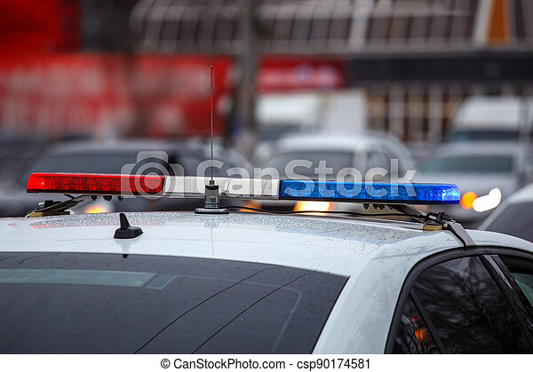 police car lights in city street at winter day with cars traffic in blurry background - csp90174581