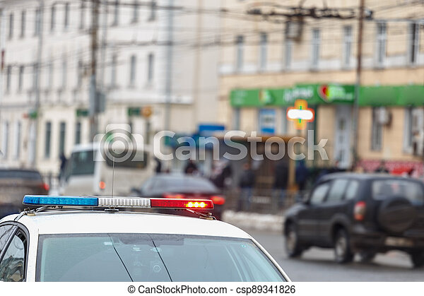 police car lights in city street with civilian cars traffic in blurry background in Tula, Russia - csp89341826