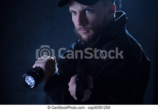 Policeman using flashlight - csp30351259