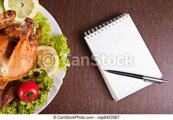 Mesa de restaurante con pollo asado, cuaderno y bolígrafo - csp6423367