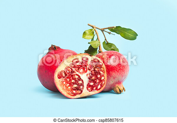 Pomegranates with branches and leaves on a light blue background - csp85807615