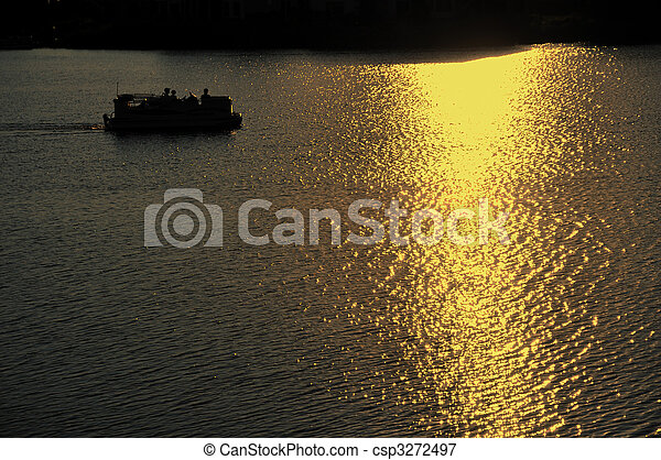 Pontoon Boat Motoring on Lake at Sunset - csp3272497