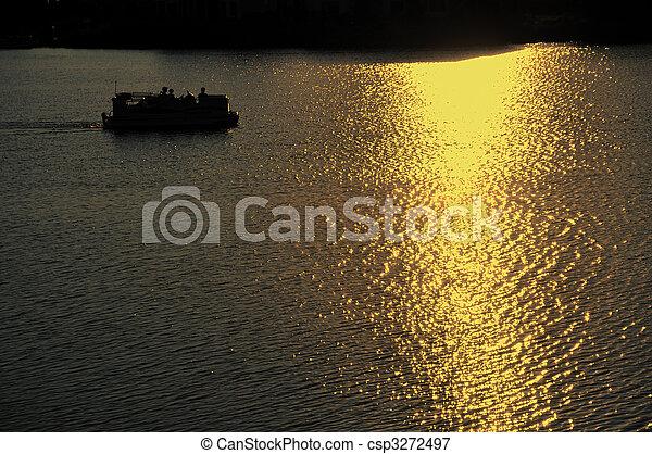 Pontoon Boat Motoring on Lake at Sunset - csp3272497