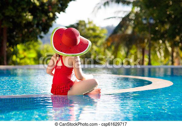 Niño con sombrero en la piscina. Vacaciones tropicales - csp61629717