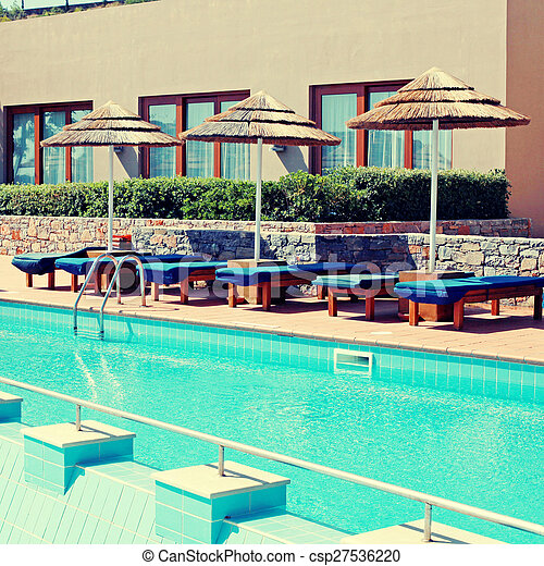 poolside with pool bed and umbrella in luxury resort  - csp27536220