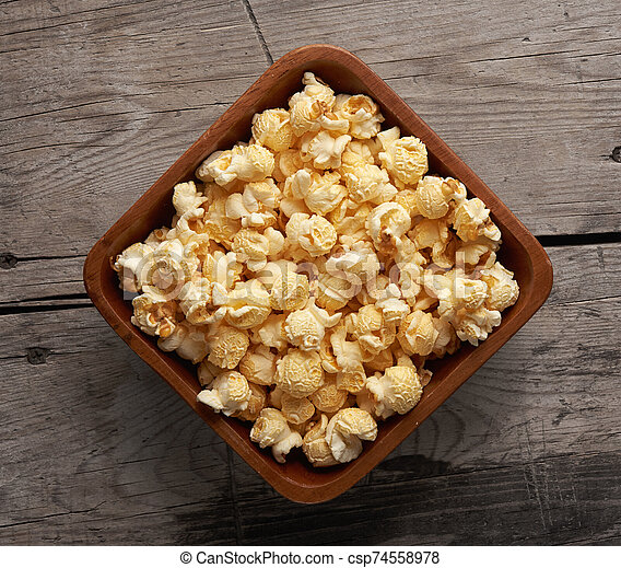 popcorn in a bowl on wooden table. Top view - csp74558978