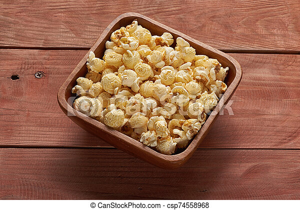 popcorn in a bowl on wooden table. Top view - csp74558968