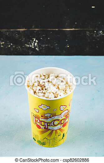 Popcorns in a yellow box on black background - csp82602886