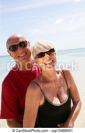 Una pareja mayor caminando por una playa - csp10468401