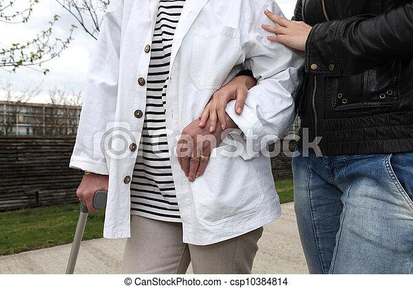 Ayudante ayudando a una persona mayor a caminar - csp10384814